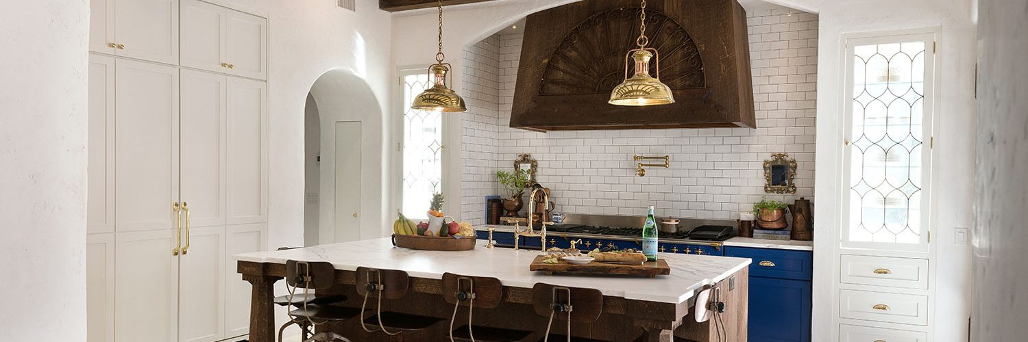 Kitchen with blue cabinets surounding professional range, rustic island with stools and white built in pantry cabinets