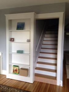 Staircase hidden by custom built rolling bookshelf