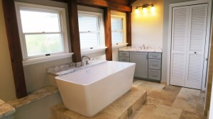 Bathroom with vessal tub and light gray vanity cabinets